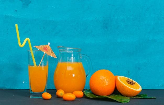 シアンの織り目加工の表面にガラス、葉、オレンジのジュースのセットです。側面図。