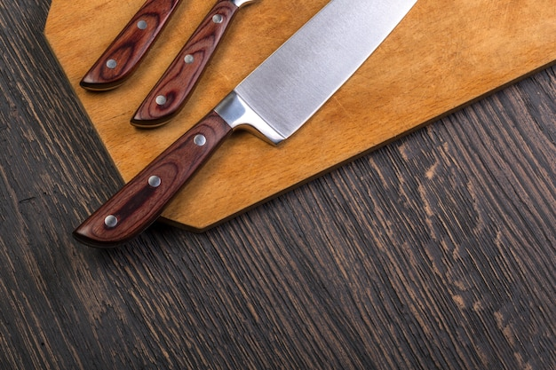 Набор кухонных ножей на деревянной разделочной доске на старом деревянном столе