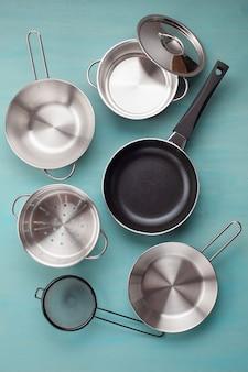 부엌 금속 프라이팬의 집합입니다. 모형, 주방 용품, 레시피 북 및 요리 수업 개념