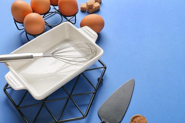 Набор кухонной утвари и ингредиентов для приготовления выпечки на цветном фоне