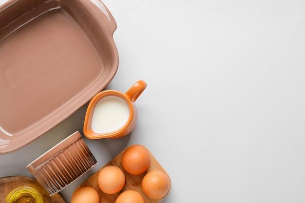 Набор кухонной утвари и ингредиентов для приготовления выпечки на светлом фоне