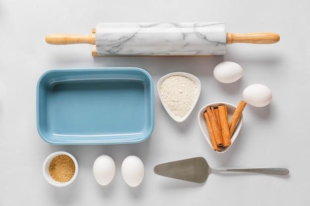 明るい背景でパン屋を準備するための台所用品と材料のセット
