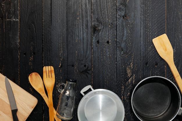 黒い木製の背景に台所用品のセット