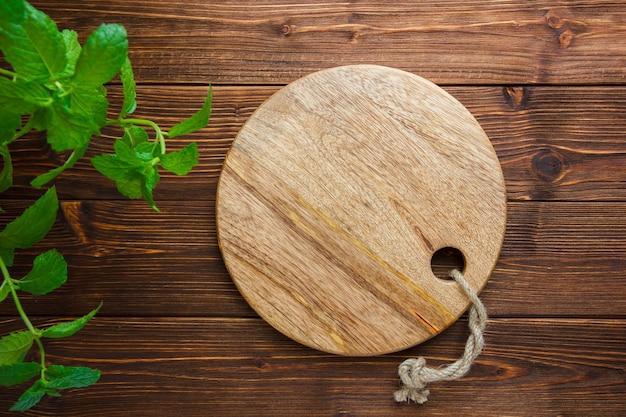 木製の背景の葉とまな板のセットです。上面図。テキスト用のコピースペース
