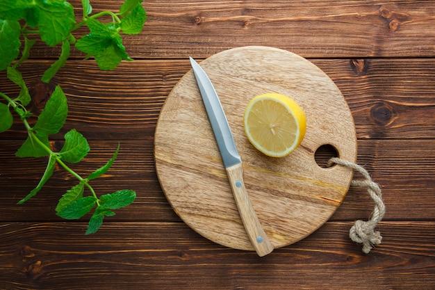 Набор листьев, деревянный нож, разделочная доска и половина лимона на деревянной поверхности. вид сверху. скопировать место для текста
