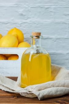 Набор лимонов на деревянном ящике и лимонного сока на деревянной поверхности. вид сбоку. место для текста