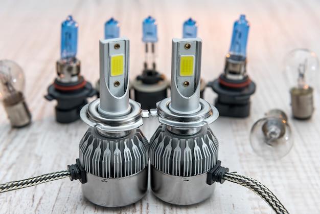 白い木製の机の上の車のランプの電球のセット。修理車両用の最新技術の電球。照明器具