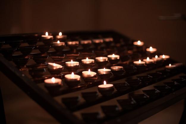 Набор зажженных свечей в церкви. надежда, молясь концепция.