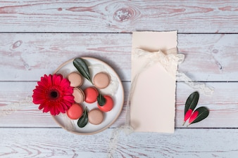 Set of macaroons and flower on plate near paper and petals