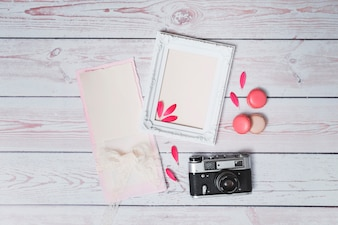 Set of macaroons near photo frame, retro camera and paper