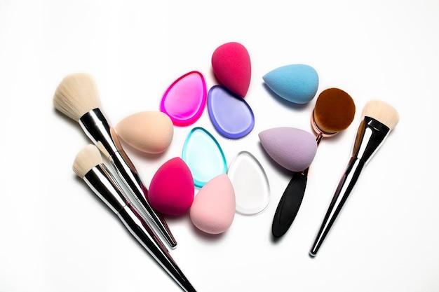 Набор кистей для макияжа, бьюти-блендеров, силиконовых губок и овальной кисти на белом фоне