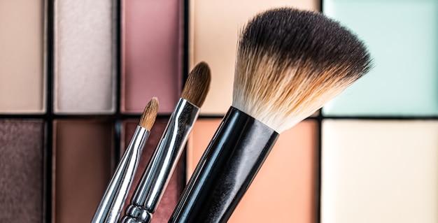 Набор кистей для макияжа на фоне палитры теней