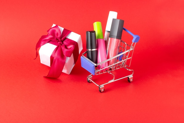 真っ赤な背景に顔の口紅、マスカラ、ギフトボックス、ショッピングカートの化粧のセットです。化粧品、オンラインストア、休日を購入する概念