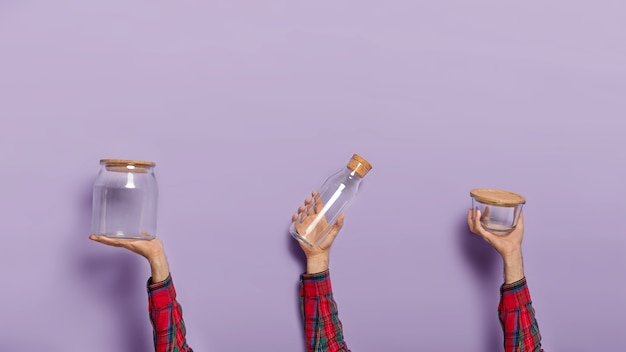 Набор мужских рук держит пустую стеклянную банку, бутылку и контейнер с органической крышкой
