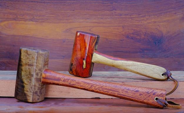 오래된 작업대의 작업장에서 목수가 사용하기 위해 태국에서 손으로 만든 자단과 파닥 나무 도구로 만든 망치 망치 세트