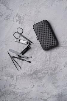 Набор маникюрных, педикюрных инструментов и аксессуаров с футляром на каменно-бетонной поверхности