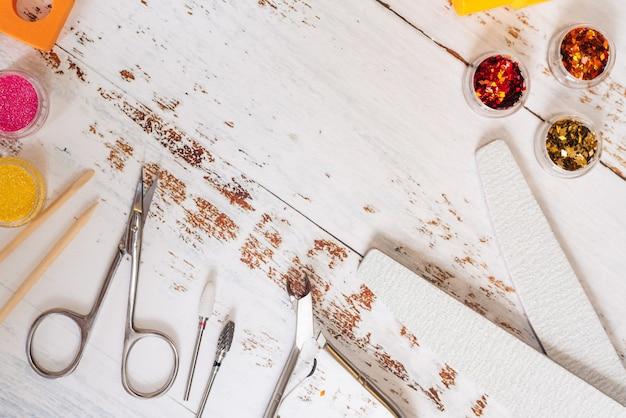 白い木製の背景にマニキュアツールとマニキュアのセット。