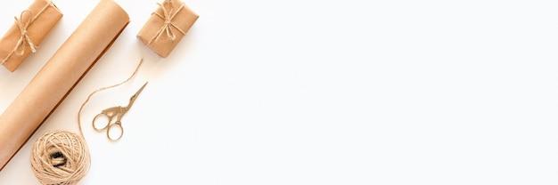 ホリデーギフトを梱包するための材料のセット。クラフト紙、ジュートより糸、はさみ、白い背景の上のボックスで作られたバナー。