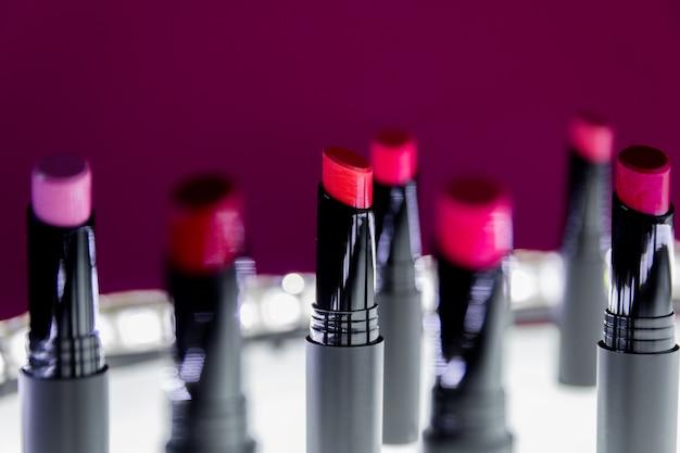 赤と白とピンクの自然な色のマット口紅のセット。ファッションのカラフルな口紅。プロのメイクと美容。点滅ボケ。