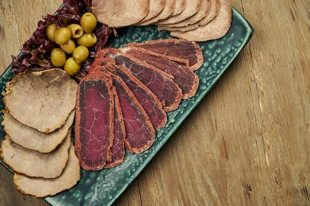 Набор мясных закусок - ломтики запеченного языка, ветчины, отварной свинины и бастурмы на синюю тарелку на деревянной поверхности. пивная закуска