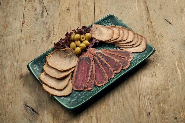 Набор мясных закусок - нарезанный запеченный язык, ветчина, вареная свинина и бастурма на синюю тарелку на деревянном столе. пивная закуска