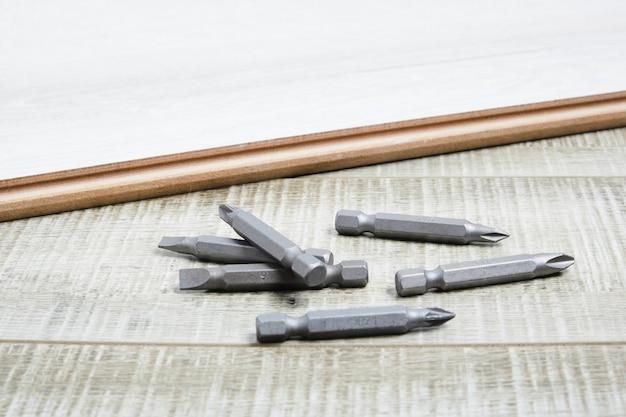 Набор металлических бит для отвертки на деревянной поверхности копией пространства