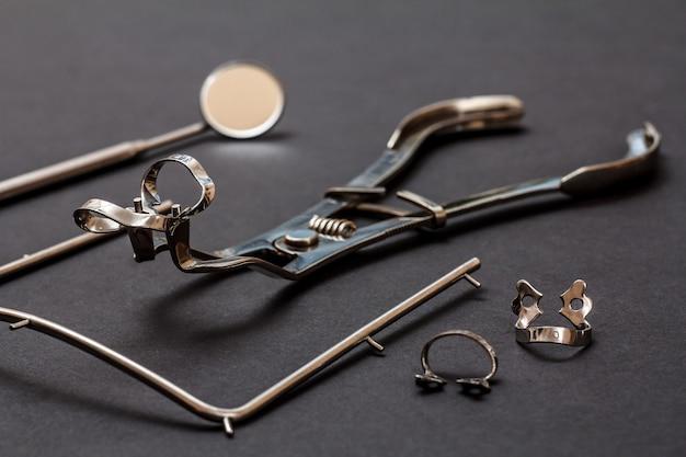 치과 치료를 위한 금속 치과 기구 세트. 검정색 배경에 있는 치과용 거울, 걸쇠, 걸쇠 및 코퍼담 프레임용 집게. 의료 도구. 필드의 얕은 깊이.