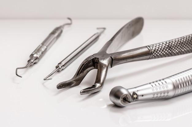 흰색 바탕에 치과 치료를 위한 금속 치과 도구 세트. 의료 도구. 클로즈업 보기입니다. 필드의 얕은 깊이. 스테인리스 스틸 치과 집게에 초점을 맞춥니다.