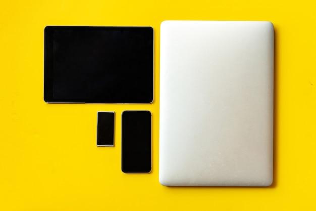 テーブル、ラップトップ、タブレット、スマートフォンのモダンなガジェットのセット