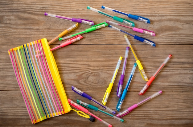 Набор разноцветных гелевых ручек на деревянном фоне
