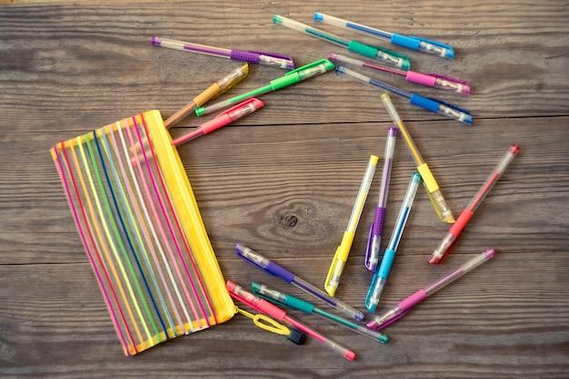 Набор разноцветных гелевых ручек на деревянном столе.