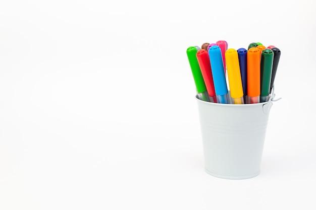 Набор разноцветных маркеров в светло-синем ведре на белом фоне крупным планом. рисование фломастерами, карандашами, тушью, инструментами художника, творчество, досуг, хобби. красочные школьные принадлежности.