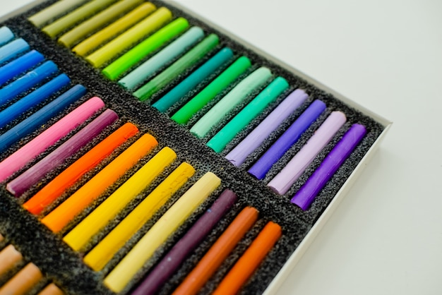 Набор разноцветных пастельных мелков в openartist коробке на белом фоне, вид сверху.
