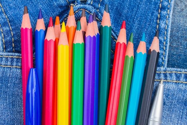 청바지 주머니에 여러 가지 빛깔 된 연필 세트를 닫습니다.