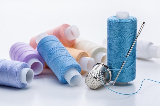Набор разноцветных ниток на катушках, большая игла для шитья и наперсток.
