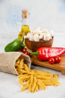 Набор грибов, оливкового масла первого холодного отжима, пасты, помидоров черри и перца чили на куске мрамора.