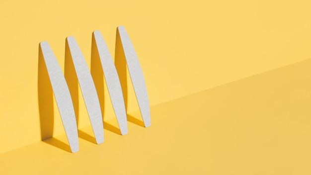 Набор пилок, наждачной доски для ногтей разной формы и разной жесткости на желтом фоне. изометрическая диагональная проекция. минимал, модные тени, современное фото. макияж для мастера по маникюру