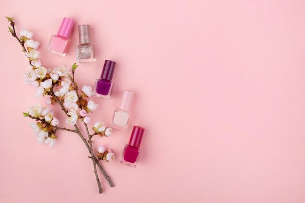 Набор лаков для ногтей и цветов на розовой стене. концепция красоты, плоская планировка с пространством для текста.