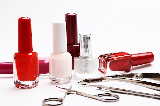Набор лаков для ногтей и инструментов для маникюра на белом фоне.