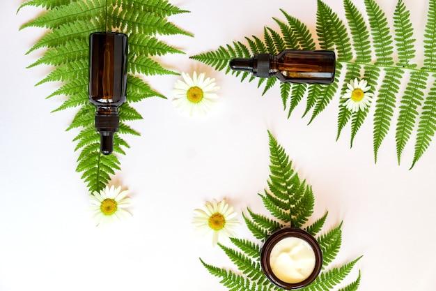 カモミールの花とシダの葉と天然ハーブ化粧品のセット。植物とハーブが入った暗いガラス瓶に入ったフェイスクリームと美容液