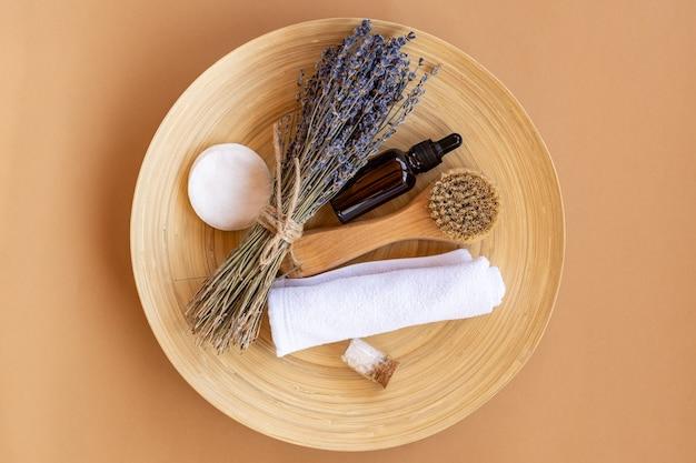 대나무 접시에 라벤더 에센셜 오일과 욕실 액세서리가 있는 천연 유기농 화장품 세트. 지속 가능한 소비.