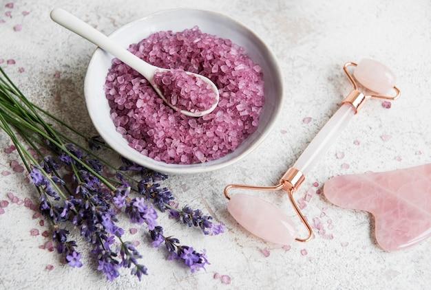 라벤더와 천연 유기농 spa 화장품 세트. 대리석 배경에 평평한 목욕 소금과 얼굴 롤러. 피부 관리, 미용 치료 개념