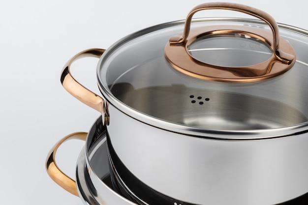 白い背景の上の新しい金属鍋のセット