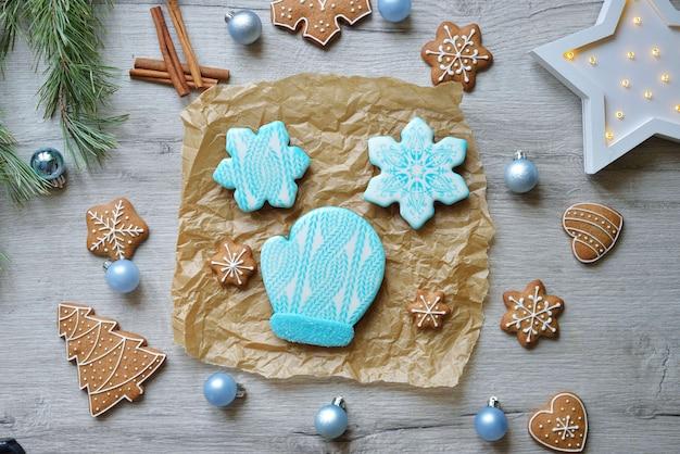 新年の装飾が施されたテーブルの上の青い釉薬で新年のジンジャーブレッドクッキーのセット。クリスマスのベーキングの概念。