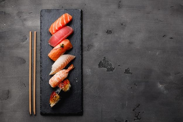 灰色の背景のプレートで提供されるにぎり寿司のセット
