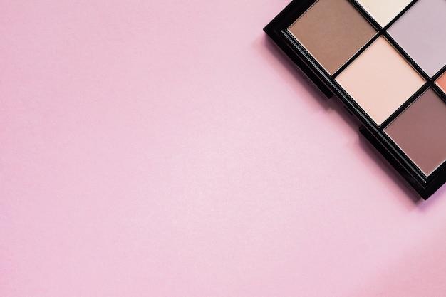 ピンクの背景に黒のケースで裸のアイシャドウのセット。トップビュー、コピースペース
