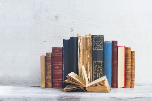 Набор старых книг с открытой одной на белом деревянном столе