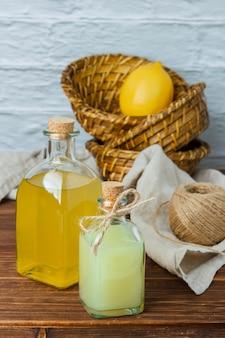 Набор на кусок белой ткани, листья лимона и лимон и сок в корзине на деревянной поверхности. высокий угол обзора. место для текста
