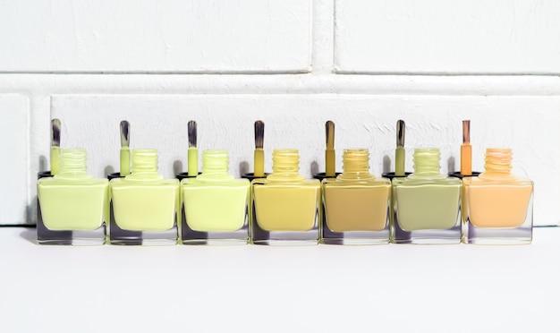 Набор открытых бутылок лака для ногтей зеленого оттенка с кистями. группа лака для ногтей на белом фоне стены. скопируйте пространство.