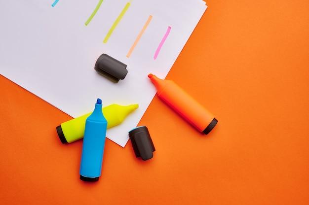 ストロークで紙のシートに開いたカラフルな油性マーカーのセット。オフィスの文房具、学校や教育の付属品、書き込みおよび描画ツール